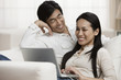 Japanese couple looking at laptop