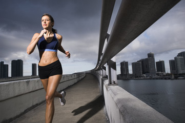 Hispanic woman running near urban waterfront