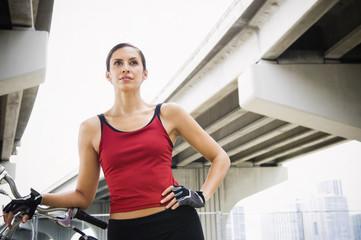 Hispanic woman standing in urban area with bicycle