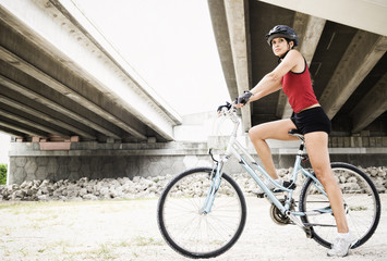 Hispanic woman riding bicycle in urban area