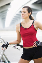 Hispanic woman standing with bicycle in urban area
