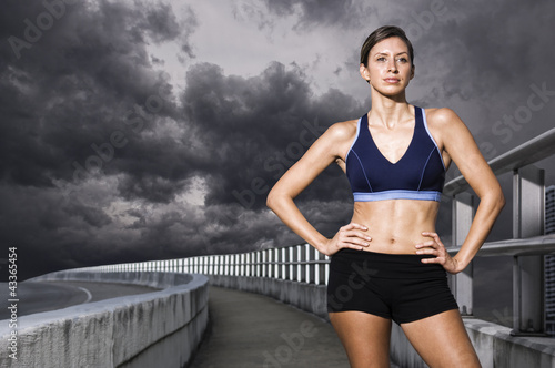 Hispanic woman in sportswear standing with hands on hips