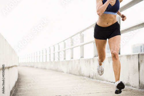 Hispanic woman running on urban walkway