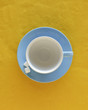 Empty coffee cup and saucer with sugar cubes, top view