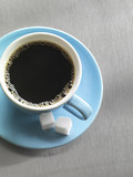 Coffee in blue cup and saucer, top view