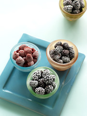 Cups of raspberries, marion berries and blackberry on serving tray