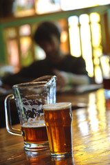 Pitcher and pint of beer on bar