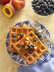 Wheat flour waffles served with blueberry and peach garnish