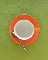 Empty coffee cup and saucer with tea spoon, top view
