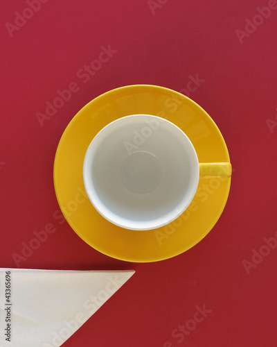 Empty coffee cup and saucer with napkin, top view