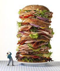 Toy man confronting world's largest sandwich