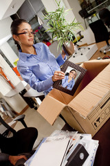 Fired Hispanic businesswoman packing box