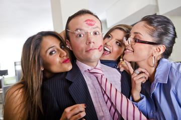 Businesswomen kissing male co-worker