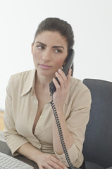 Hispanic businesswoman talking on telephone