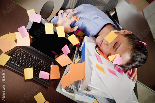 Hispanic businesswoman covered in sticky notes sleeping at desk