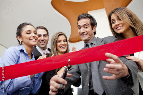 Hispanic co-workers watching businessman cutting red ribbon