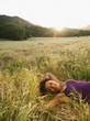 Mixed race woman laying in remote field