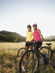 Friends standing in field with mountain bikes