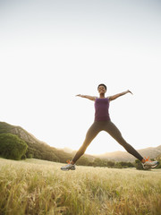 Mixed race woman jumping in remote field