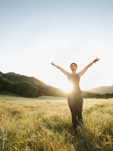 Mixed race standing in remote field with arms outstretched