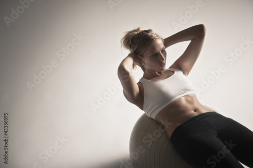 Caucasian woman doing sit-ups on exercise ball