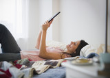 Brazilian woman using digital tablet in bed