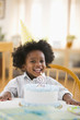 Grinning African American boy sitting with birthday cake