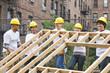 Volunteers lifting construction frame together