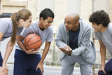Coach talking to basketball players during game