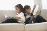 Brother and sister reading books together