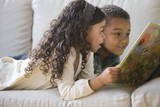 Brother and sister reading book together