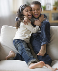 Brother and sister hugging on sofa