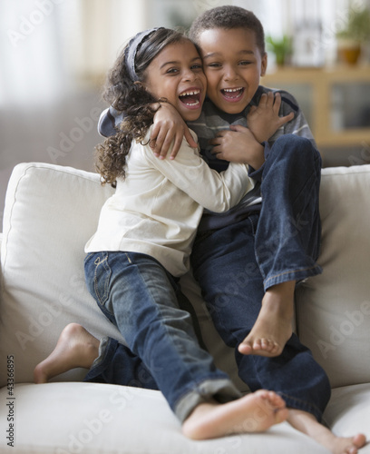 Brother and sister hugging on sofa