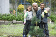 Grandfather and grandchildren planting a tree together