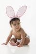 Mixed race baby girl wearing bunny ears