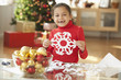 Hispanic girl making Christmas paper snowflake