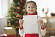 Hispanic girl writing Christmas letter to Santa