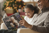 Father reading Christmas book to daughter