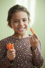 Mixed race girl eating carrot sticks