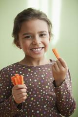 Mixed race girl eating carrot sticks