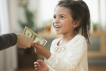 Mother handing girl one dollar bill