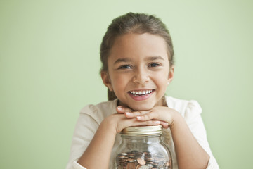 Mixed race girl holding jar full of coins