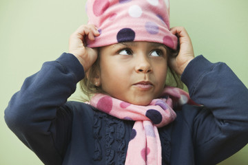 Mixed race girl putting on knit cap