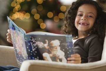 Hispanic girl reading Christmas book