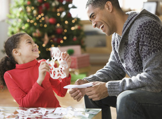 Father and daughter making Christmas paper snowflakes