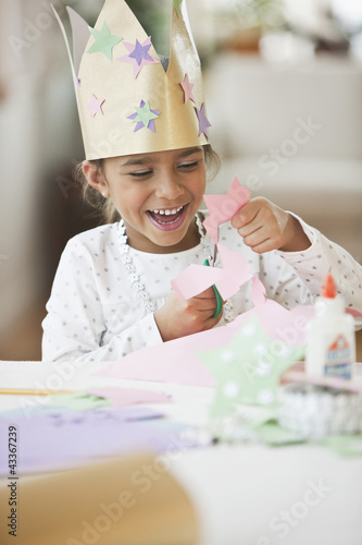 Mixed race girl in crown cutting paper