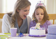 Mother watching daughter blowing out birthday candle