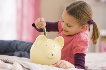 Mixed race girl putting money into piggy bank