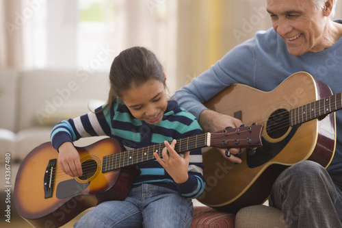 Grandfather teaching granddaughter how to play guitar