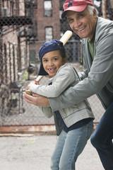 Coach teaching girl to play baseball